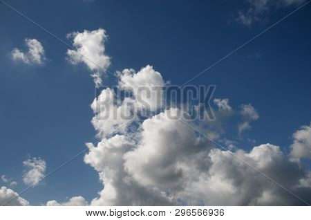 A Beautiful Vibrant Sky Cloudscape Scene, With White Coloured Billowing Cumulonimbus Cloud Formation