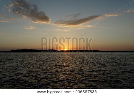 A Natural Tranquill Orange Coloured Cumulus Cloudy Ocean Sunset Seascape Over Sea Water With Water R