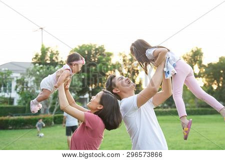 Happy Family Concept. Asian Father And Mother Holding And Raising Their Children Up Into The Air. Th
