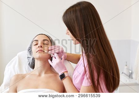 Indoor Shot Of Attractive Young Woman Gets Beauty Facial Injections. Anti-aging, Nourishing, Vitamin