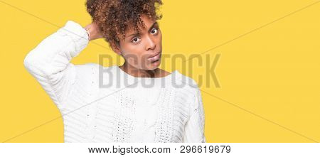 Beautiful young african american woman wearing winter sweater over isolated background confuse and wonder about question. Uncertain with doubt, thinking with hand on head. Pensive concept.
