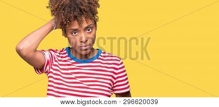 Beautiful young african american woman over isolated background confuse and wonder about question. Uncertain with doubt, thinking with hand on head. Pensive concept.