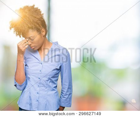 Beautiful young african american business woman over isolated background tired rubbing nose and eyes feeling fatigue and headache. Stress and frustration concept.