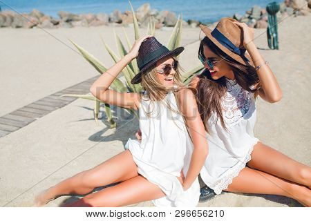 Two Attractive Brunette And Blonde Girls With Long Hair Are Sitting On The Beach Near Sea. They Wear