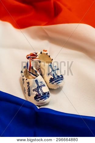 Mini Ceramic Clogs From Holland On Dutch Flag Background