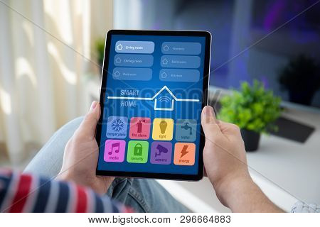 Man Hands Holding Computer Tablet With App Smart Home On Screen In The Home Room