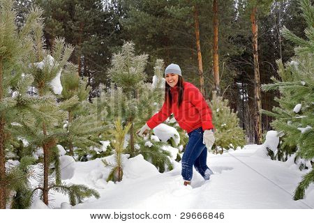 Happy pretty young woman in the red jacket is selecting a tree.