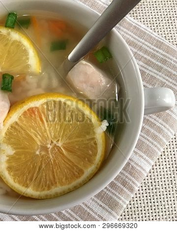 Delicious Chicken Soup With Lemon, Rise, Carrot And Green Onion. Top View. Soup With A Spoon On A Ta