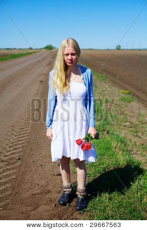 Sad young woman holding red tulips standing in russian field near ground road wearing rubbers