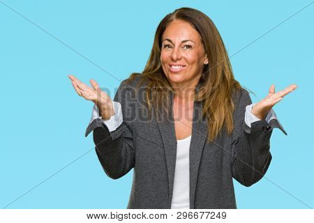 Middle age adult woman wearing oversize boyfriend jacket over isolated background clueless and confused expression with arms and hands raised. Doubt concept.
