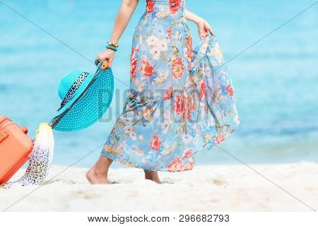 Travel Plan. Hand Women Traveler Holding Orange Luggage Walking On The Beach. Traveler And Tourism P