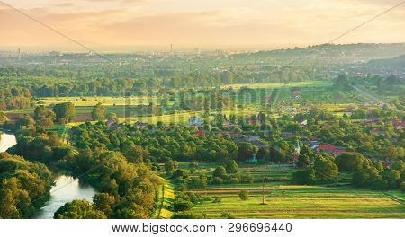 Evening Countryside Scenery In Springtime. Village, Agricultural Fields And River In The Valley. Tow
