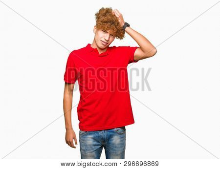 Young handsome man with afro hair wearing red t-shirt confuse and wonder about question. Uncertain with doubt, thinking with hand on head. Pensive concept.