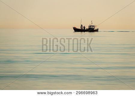 A Fishing Boat Goes Out To Sea Early In The Morning When The Sea Is Calm