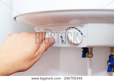 Man Turns On The Switch On Control Panel Of Home Electric Water Heater (boiler).