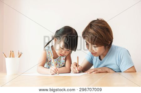 Happy Asian Mother And Her Daughter Drawing Together. Kid And Her Teacher Having Fun In Kindergarten