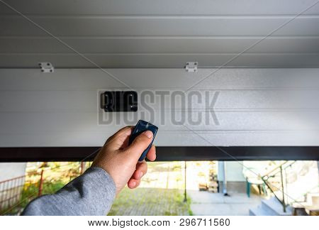 Garage Door Pvc. Hand Uses Remote Controller For Closing And Opening Garage Door