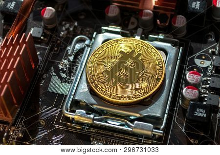 Golden physycal bitcoin among the computer components. Business concept of digital cryptocurrency. Blockchain technology and bitcoin mining concept