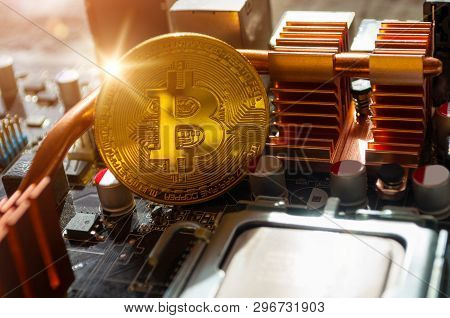 Golden physical bitcoin near the computer components. Business concept of digital cryptocurrency. Blockchain technology and bitcoin mining concept, bitcoin closeup