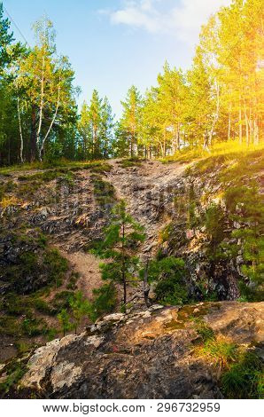 Summer forest mountain landscape - marble high steep near the Sugomak cave in Southern Urals, Russia. Summer sunset mountain view, mountain forest nature landscape
