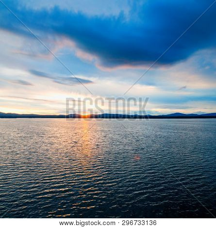 Sea sunset landscape. Sea water surface lit by sunset light. Summer sunny water scene in colorful tones. Sea summer nature with mountain range at the horizon.Summer sunny water sea scene in cold tones