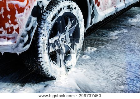 Car Wheel Close Up. Car Is Cleaning With Soap Suds At Self Service Car Wash. White Lather On Auto.
