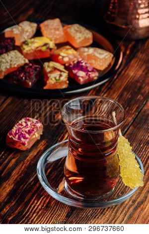 Tea in armudu glass with oriental delight rahat lokum over wooden surface poster