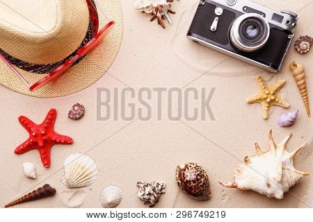 Beach Accessories - Sunglasses, Hat And Camera On Sand Witn Shells And Seastar. Concept Of Summer An