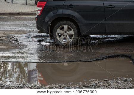 Car Hitting Pothole In City Street Splashing Muddy Water.