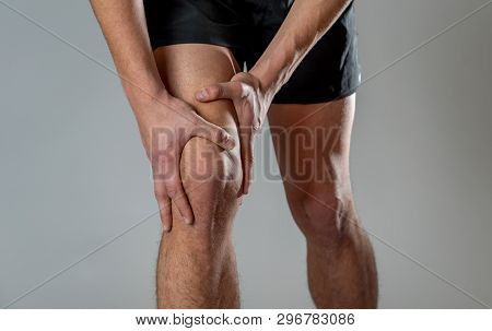 Young Fit Man Holding Knee With Hands In Pain After Suffering Muscle Injury Broken Bone Leg Pain Spr