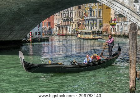 Venice, Italy - April 17 2019: Venetian Gondola With Tourist Couple In Canale Grande, The Grand Cana