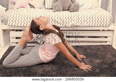 Morning Exercises. Cute Gymnast Practice Stretching Every Morning. Girl Child Stretching On Carpet.