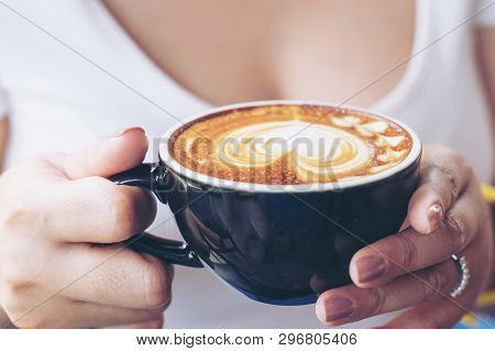 Close-up Of A Cup Of Coffee Latte Art On Woman Hand In Coffee Shop Cafe