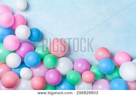 Heap Of Colorful Balloons On Blue Pastel Table Top View. Birthday Or Party Background. Flat Lay Styl
