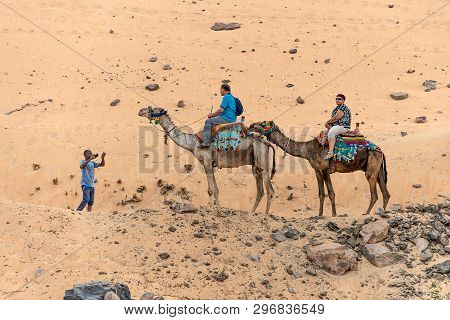 Aswan, Egypt 18.05.2018 Tourists Aboard Camel Tour To Nubian Village The West Bank Of The River Nile