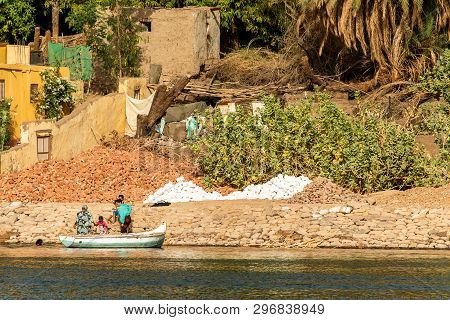 Aswan, Egypt 21.05.2018 Egyptian Family Working At The Nile River Bank