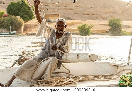 Aswan, Egypt 21.05.2018 Old Nubian Man Sitting On Felucca Boat Deck And Sailing Down The Nile River