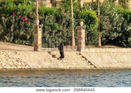Aswan, Egypt 21.05.2018 Egyptian Women Walking To The Nile River Bank