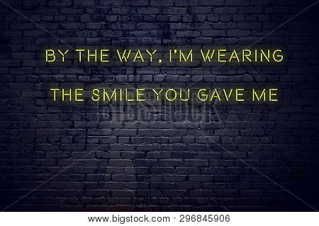 Positive Inspiring Quote On Neon Sign Against Brick Wall By The Way Im Wearing The Smile You Gave Me