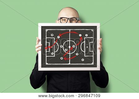 A Man In A White Shirt And Jacket Is Holding A Tablet With A Drawn Game Tactics For Football. Concep