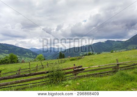 Mountain Slope With Fenced Hayfields On A Foreground On A Background Of Valley, Distant Mountains Co