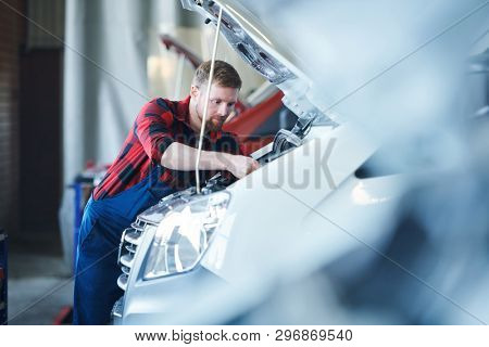Young professional master of car repair service center bending over open engine while repairing it