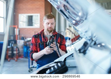 Young contemporary technician or repairman in workwear looking at data in electronic device while standing by one of cars poster