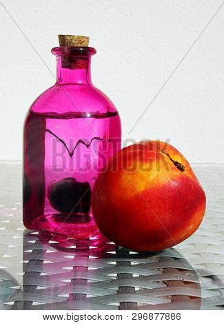 Still Life With Fresh Compote In Vintage Glass Botlle, Nectarine And Ripe Cherry Against A High Key