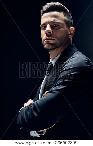 Handsome Confident Man In Black Suit With Arms Crossed On Dark Background. Young And Success Concept