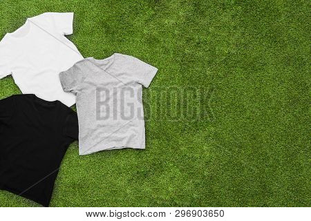 Randomly Scattered Mens Different Coloured T-shirts On Grass Background. Horizontal View.