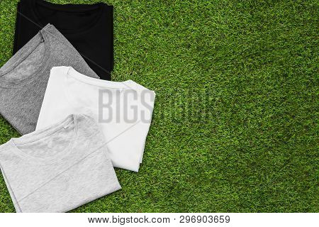 Stack Of Arranged Different Coloured Mens T-shirt On Grass Background. Horizontal View.