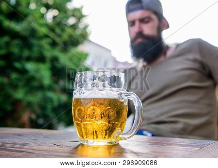 Man sit cafe terrace enjoying beer defocused. Craft beer is young, urban and fashionable. Distinct beer culture. Mug cold fresh beer on table close up. Creative young brewer. Alcohol and bar concept poster