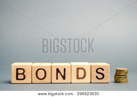 Wooden Blocks With The Word Bonds And Coins. A Bond Is A Security That Indicates That The Investor H