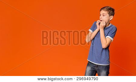 Frightened Boy Looking Aside On Copy Space And Biting His Fists In Horror Or Fright, Orange Backgrou